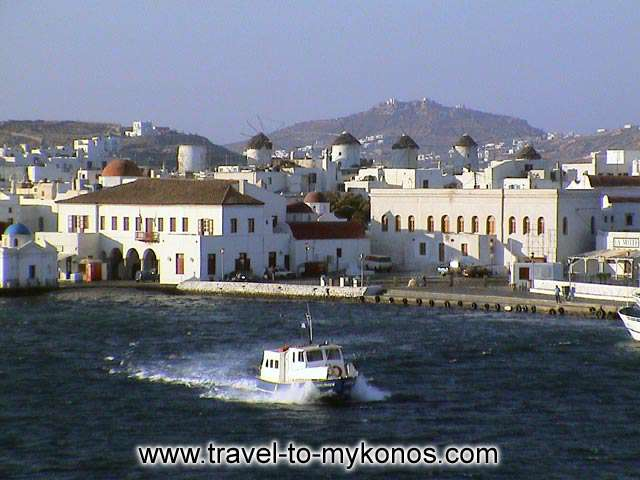 MYKONOS TOWN HALL - The coastal street, the town hall and at back the windmills.