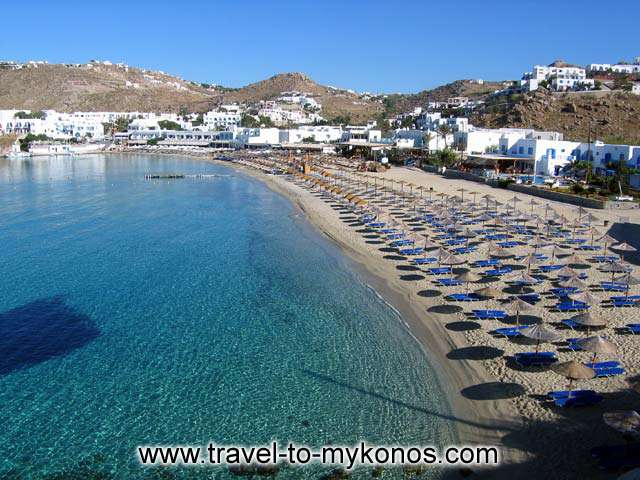 VIEW OF THE BEACH - A view of the golden sand, crystal clear water beach of Platis Gialos in Mykonos